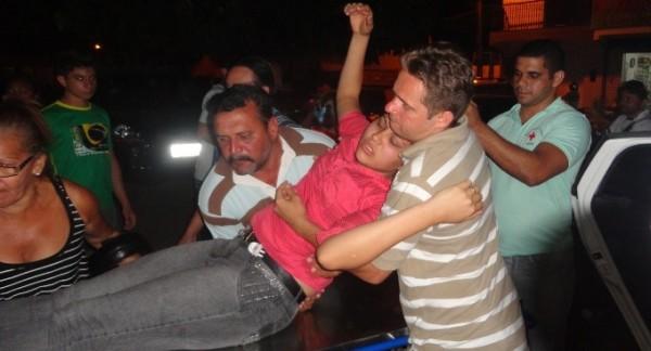 Júnior Carneiro (camisa de listra) carregando a esposa para levar ao hospital
