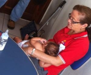 Criança nos braços de Francisca Martins, funcionaria do Conselho tutelar