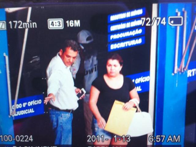 Mulher, no momento em que estava sendo libertada e ao fundo, um dos suspeitos do assalto fala ao telefone.(Foto: Reprodução/ )