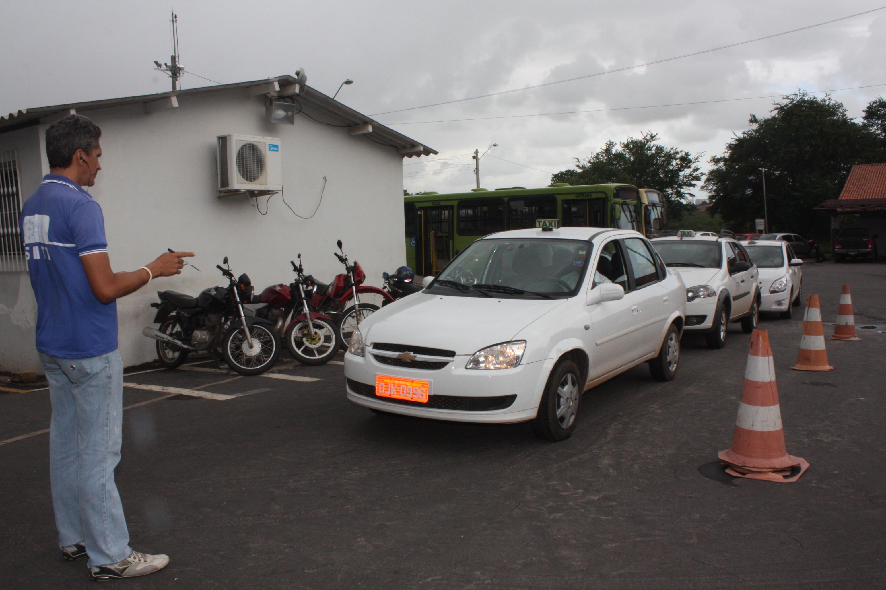 Fiscal da SMTT vistoria táxi no pátio da secretaria.