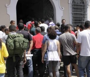 Multidão na entrada para fazer o concurso público.