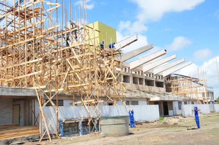 Operários trabalham na colocação de estrutura de concreto na cobertura